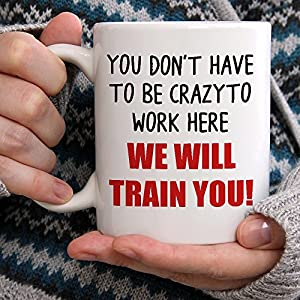 You Don't Have To Be Crazy To Work Here We Will Train You Mug - being held