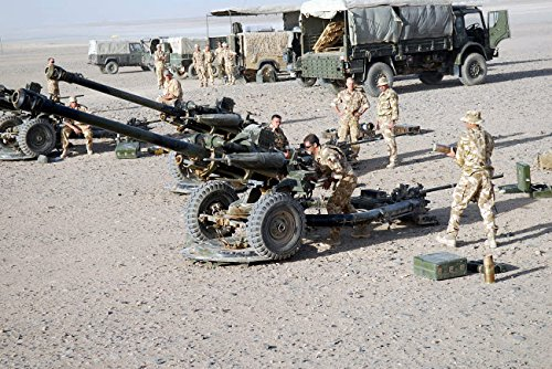 Howitzer 105mm light guns are lined up at Camp Bastion Afghanistan Poster Print by Andrew ChittockStocktrek Images (34 x 22)