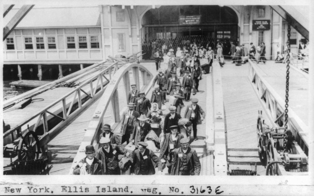 Vintography 1909 Photo York. Ellis Island Immigrants Walking Across pier from Bridge. Location: Ellis Island, Jersey, York