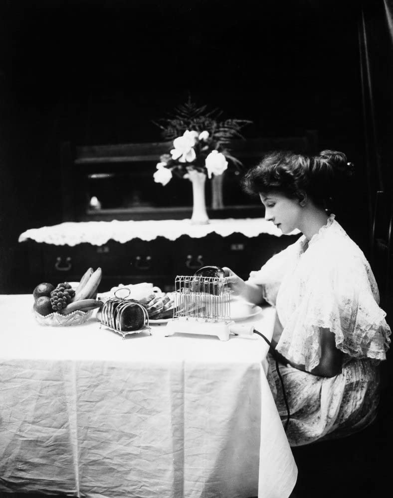 Electric Toaster 1908 Na Woman Removing A Slice Of Toast From An Electric Toaster Manufactured By General Electric Photographed In 1908 Poster Print by (24 x 36)