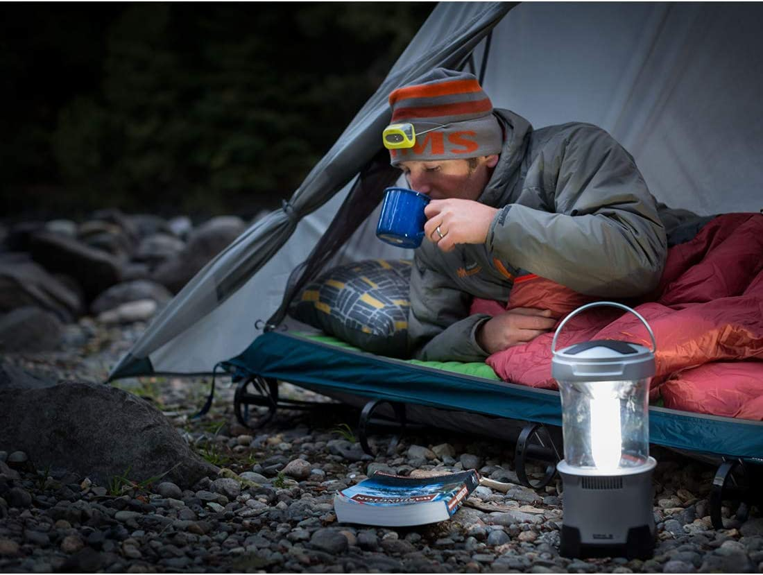 A camper lying down in the Therm-a-Rest Tent Cot drinking from a cup