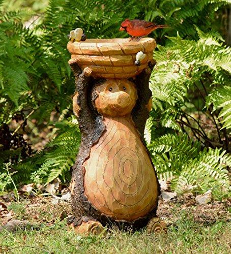 Freestanding wooden bird bath carved as a wild bear.