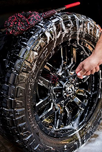 A wool wheel brush is placed on top of a car tire while another is used to wash the side of the tire.