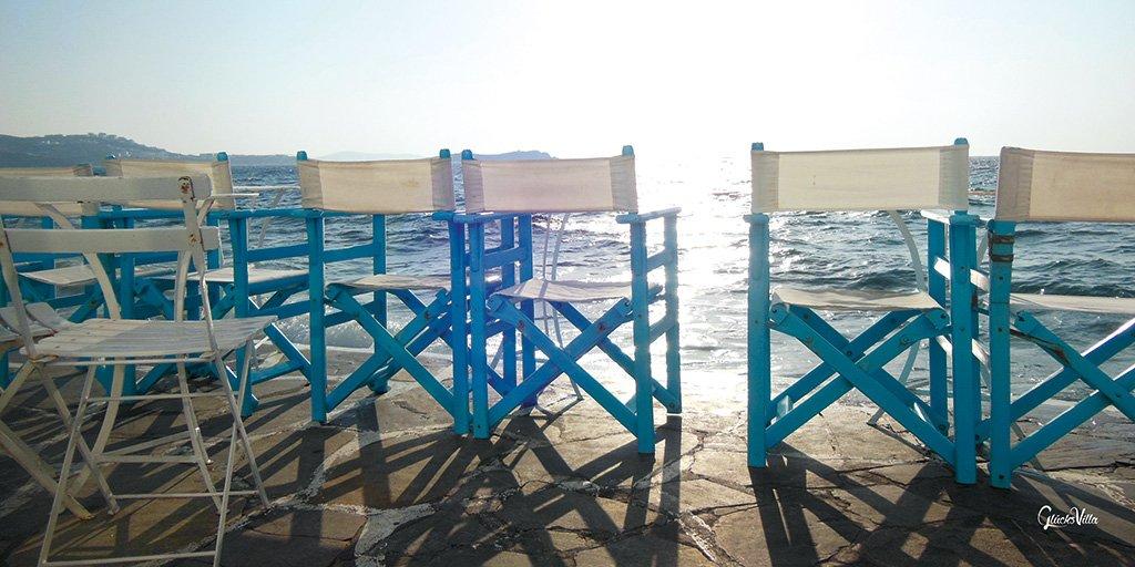 Glücksvilla Sitzgelegenheiten 2 - XXL Bild/Wandbild, Größe: 120 x 60 cm Quer-Format, Digital-Druck auf Acrylglas 5 mm. Griechenland Kykladen Taverne Tisch Stuhl Haus weiß blau Liebe groß Kunst