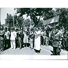 Vintage photo of People on the street, smiling, clapping their hands and cheering, some are holding banners, with police on guard, during the war in Algeria.