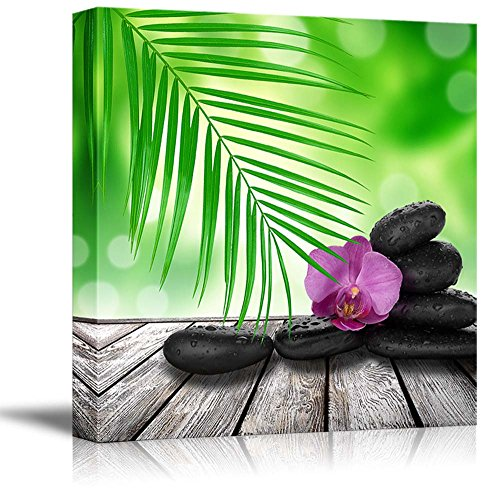 Zen Basalt Stones on a Wooden Table with Blossoming Orchid and Palm Leaf Wall Decor