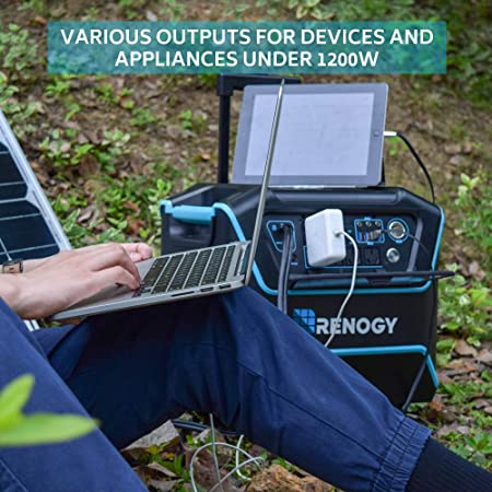 A man charging his laptop and ipad using a renogy lycan powerbox solar generator