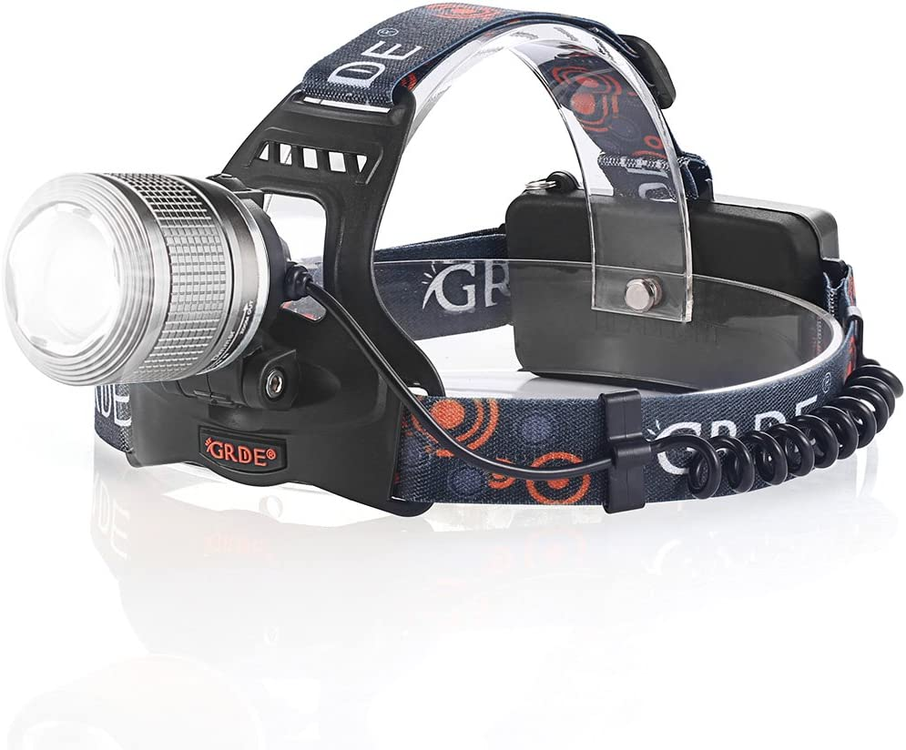 Image of a headlamp with black and orange color band, with LED on.