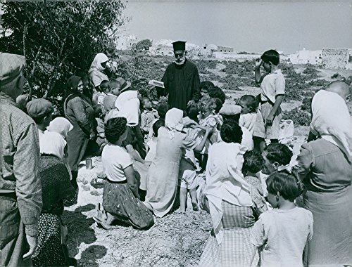 Vintage photo of Children and adults listening to a man in black toga. in an uphill, in Greece.