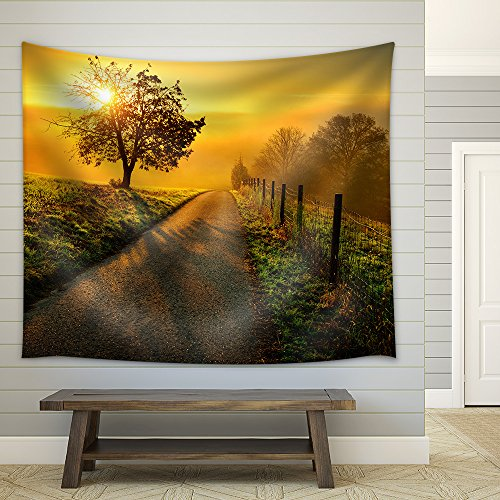 Idyllic Rural Landscape on a Hill with a Tree on a Meadow at Sunrise Fabric Wall
