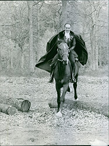 Vintage photo of Michel Piccoli wearing a suit with cape and riding a horse. -