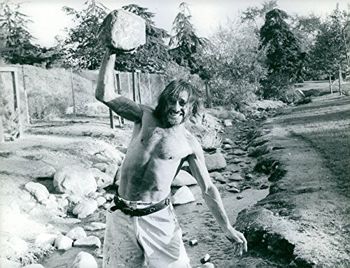 Vintage photo of Man carrying a big rock. ()