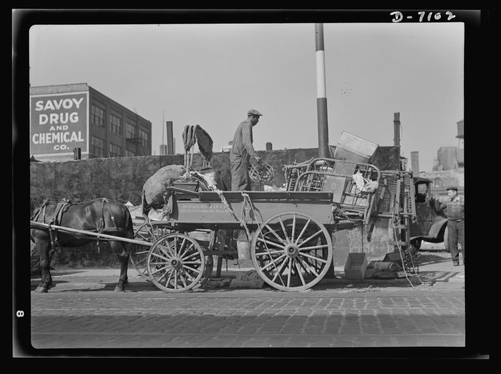 1942 Photo Salvage. Scrap for steel mills. To feed the nation's munitions furnaces, tons of scrap from America's attics and basements are collected every day. Here, a junkman unloads his wagon in a ce