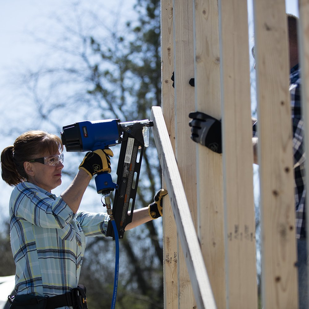 Image of lady using framing nailer to build fence
