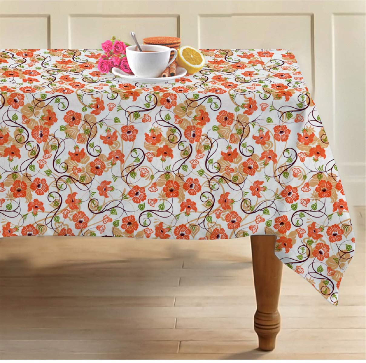 A colorful flower print table cloth with tea cup and eatables kept on it in the above picture.
