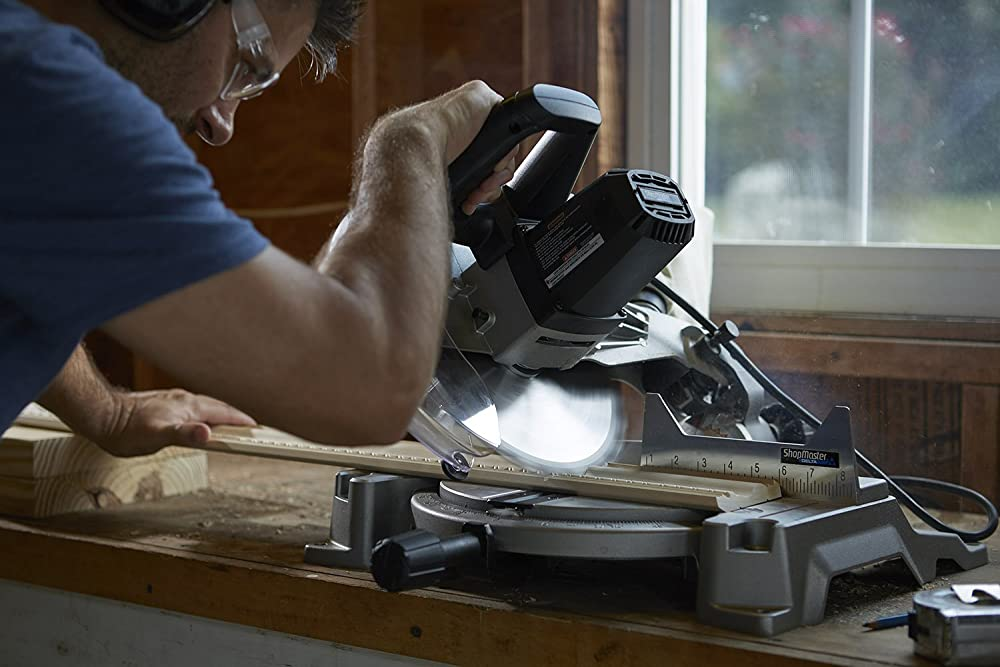 A man use miter saw to cut wood
