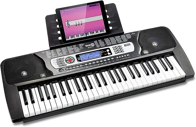 Piano RockJam con teclado de 54 teclas con fuente de alimentación, soporte para partituras, pegatinas para notas de piano y lecciones de piano.