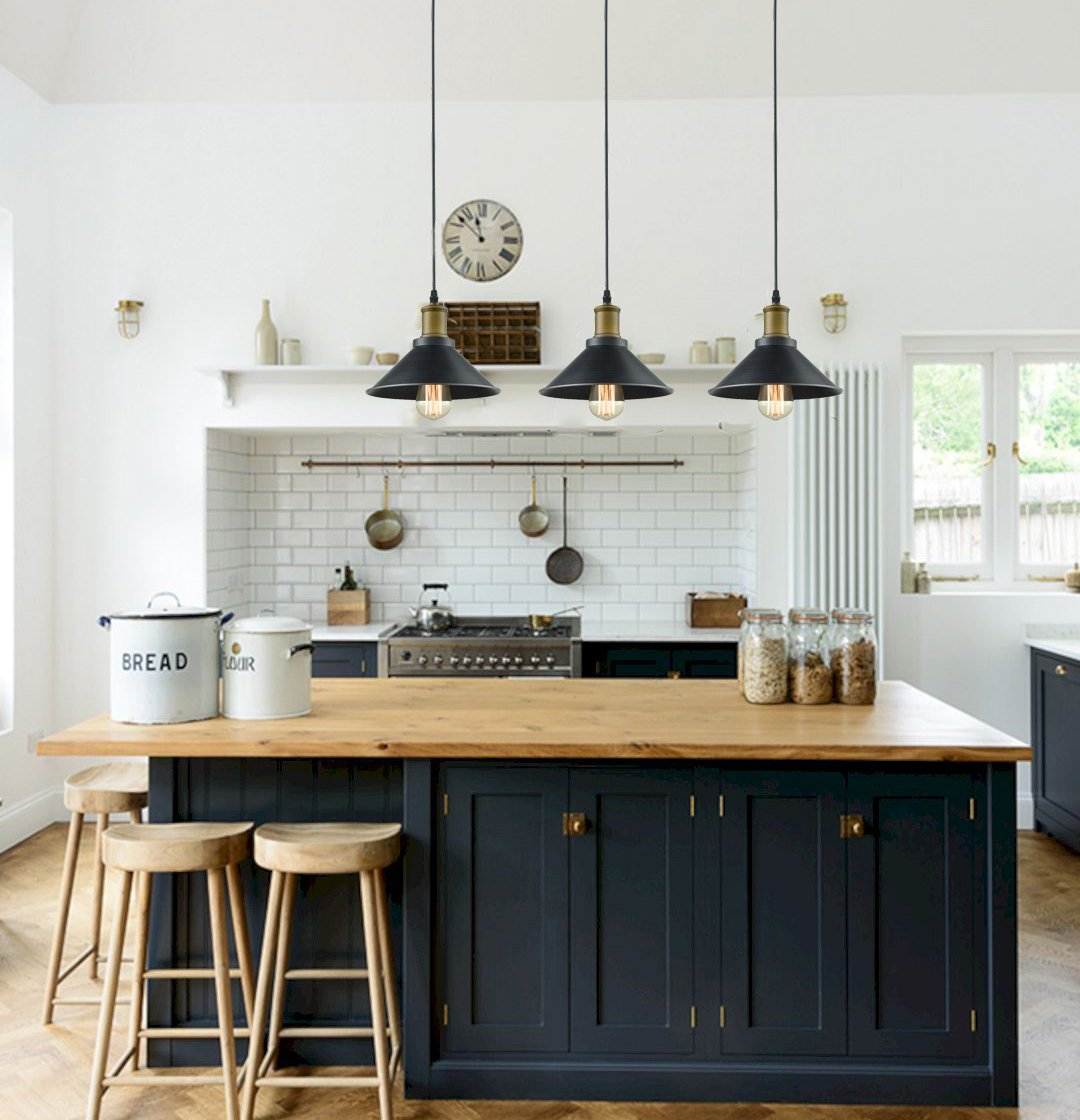 Industrial farmhouse style kitchen with black painted island, subway tile, Shaker stools, and black pendant lights over island.