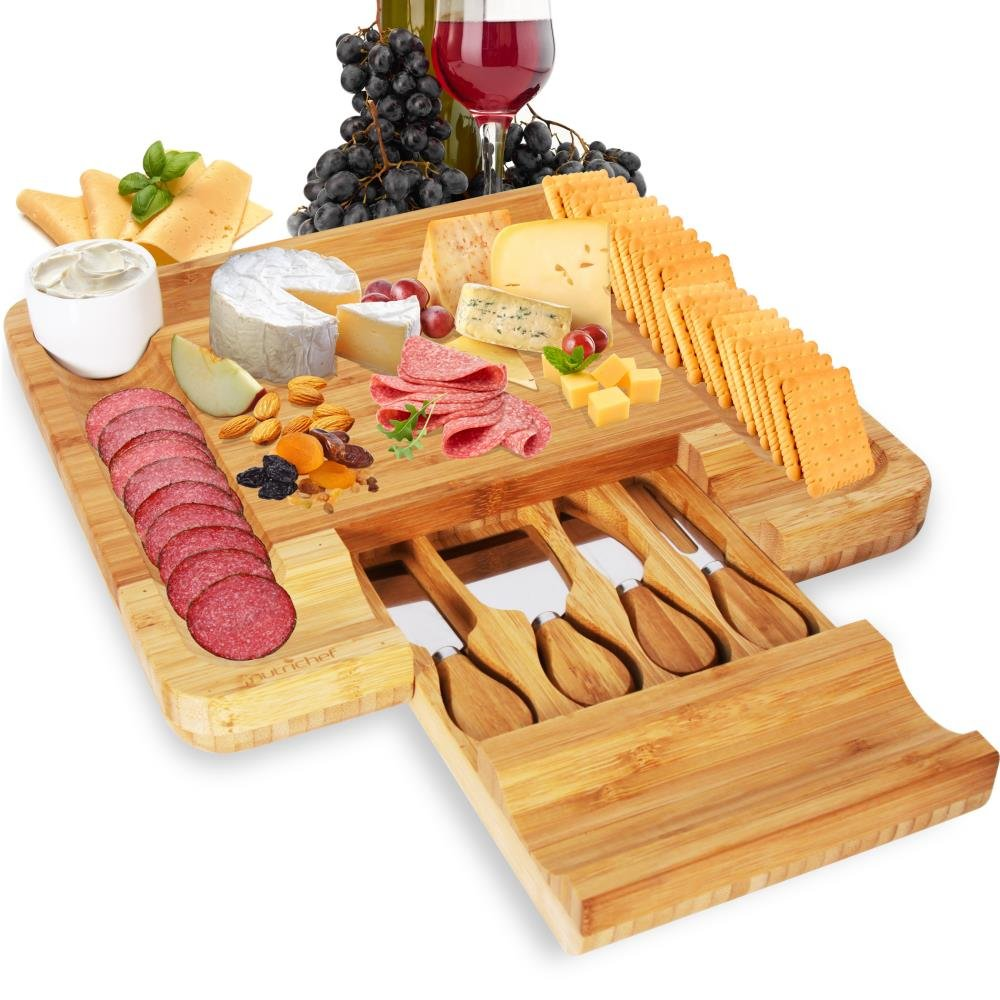 cheese board with utensils in a drawer, covered in meats and cheeses