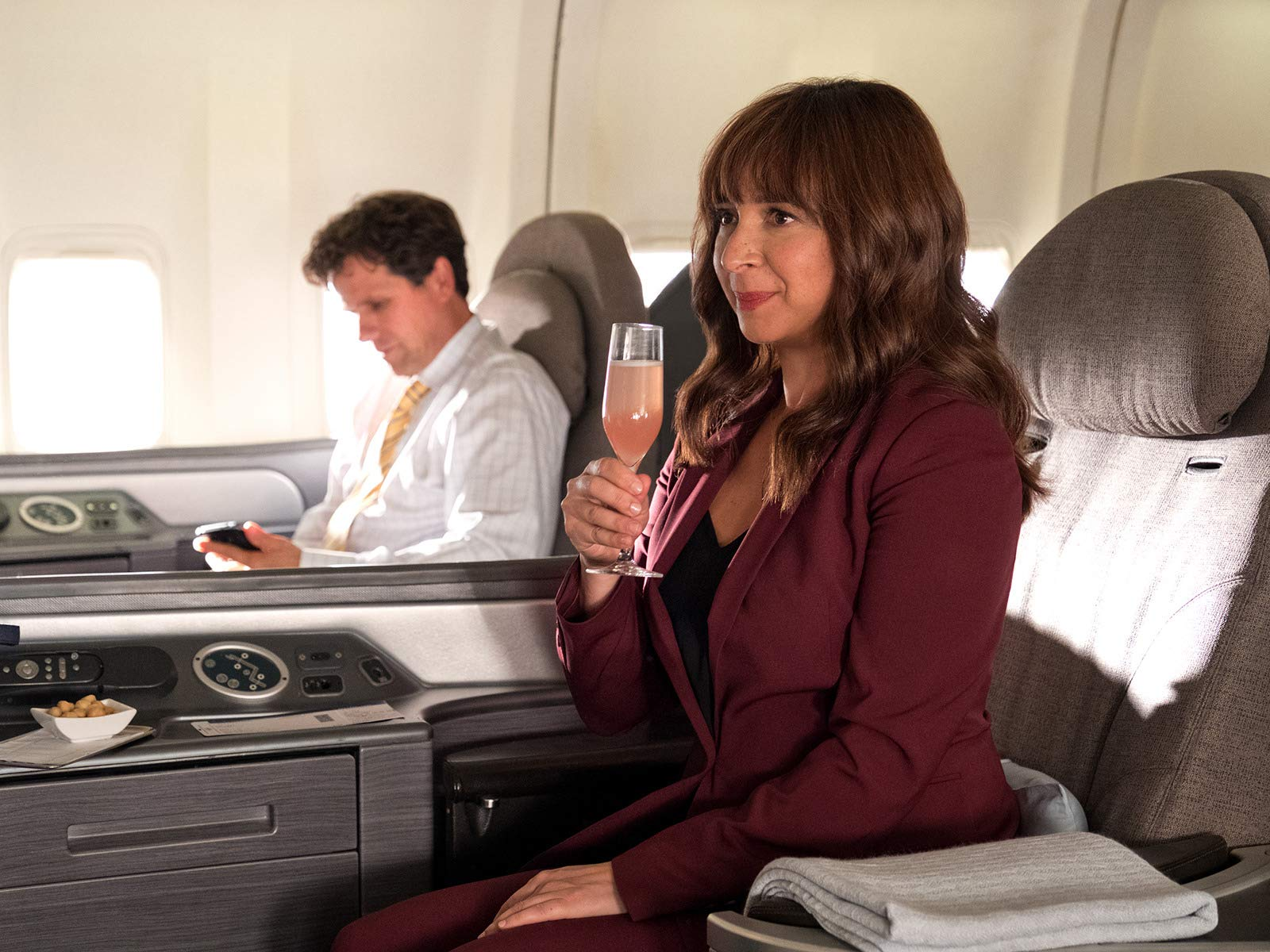 June Hoffman (Maya Rudolph) sits on an airplane with a glass of champagne in Amazon's Forever.