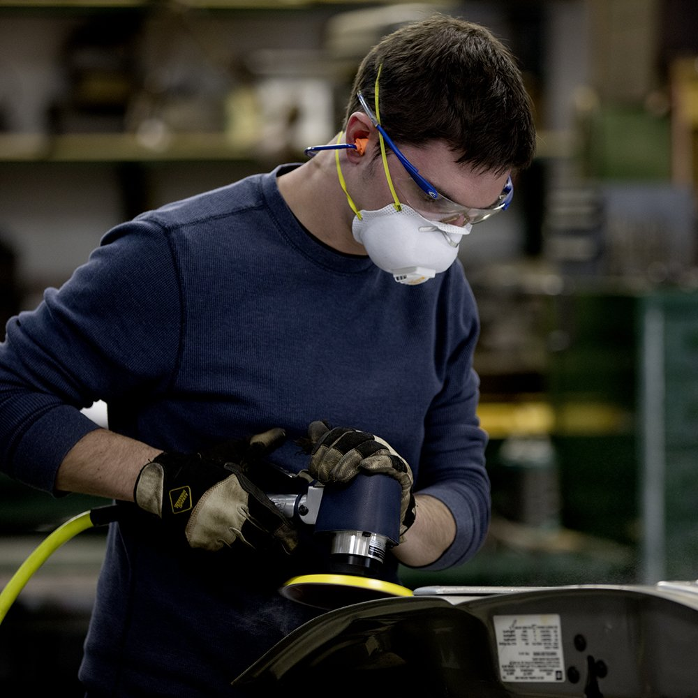 image of man in autobody shopping working with orbital sander
