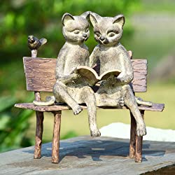 cats on bench reading statue