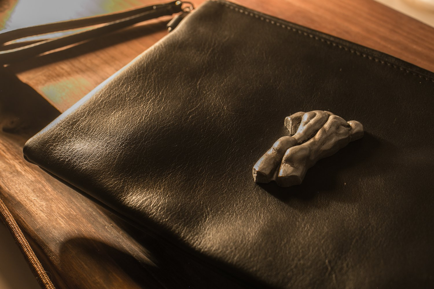 Leather zipper clutch with a sculpture of a man
