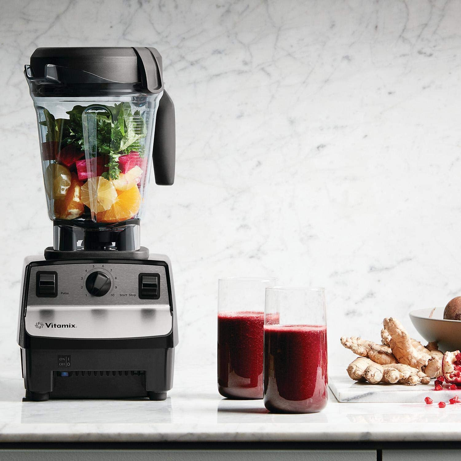 Vitamix 5300 filled with ingredients and two glasses of red fruit juice next to it.