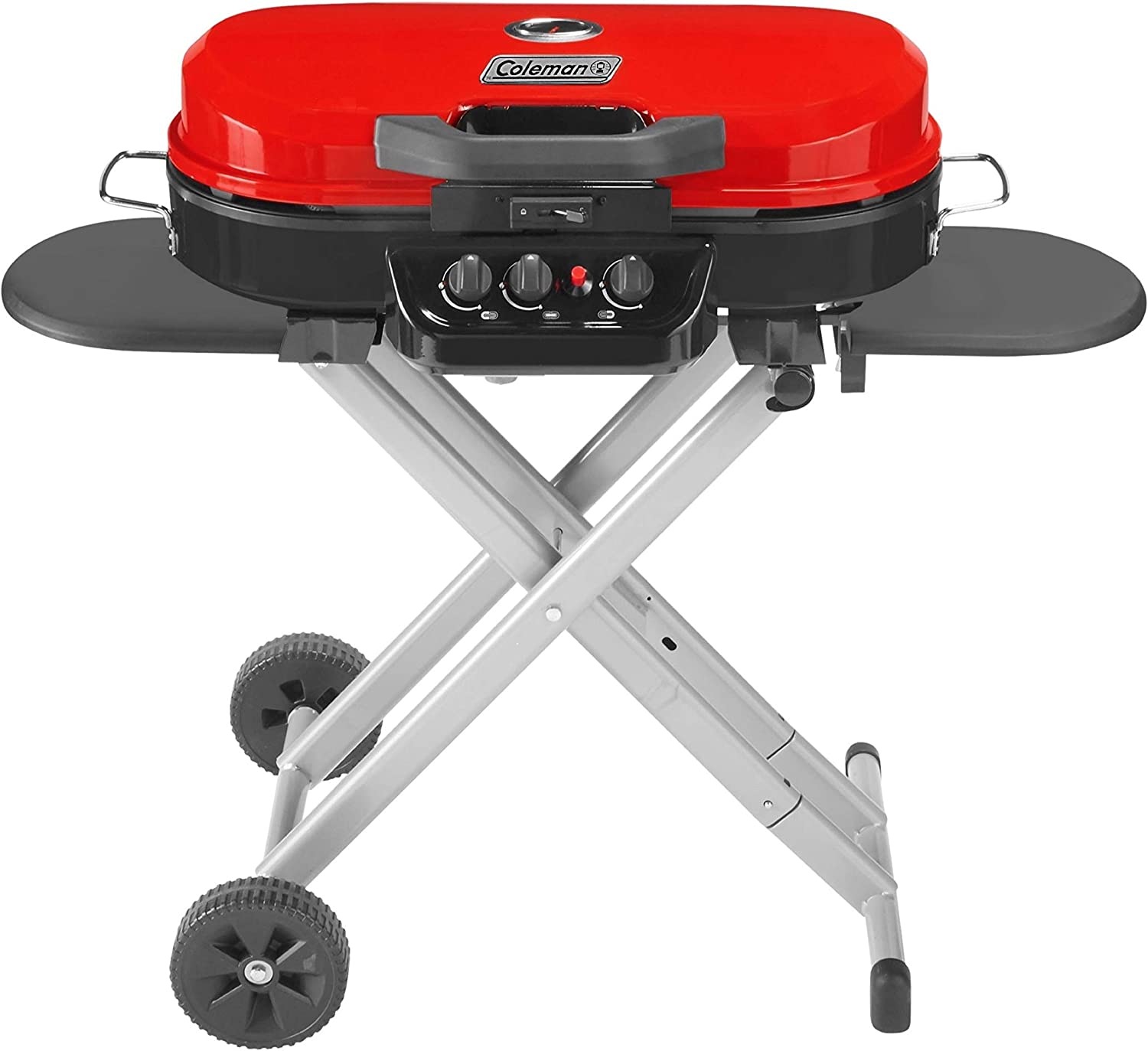 An image of the Coleman propane grill on a stand, the grill is in colors red and black combination with fuel controllers at the center.