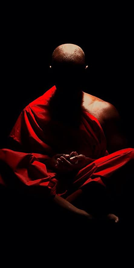 Buddhist Monk Meditating In Shadows