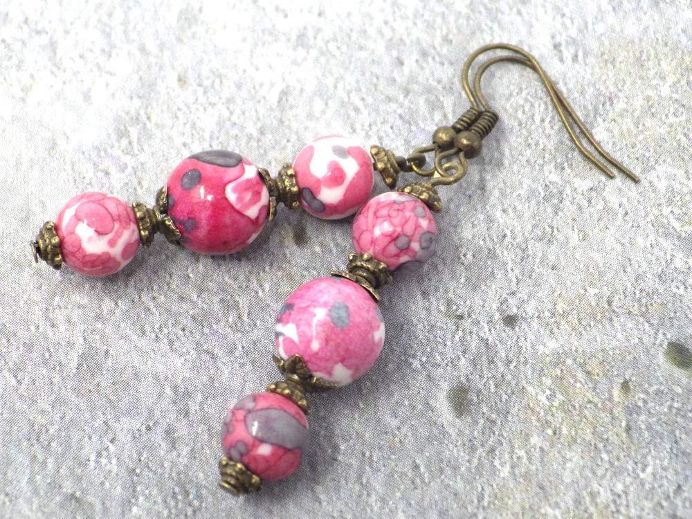 Pendientes con perlas finas en jade natural teñidas en rosa y gris, cuentas de metal y gancho francés color bronce.