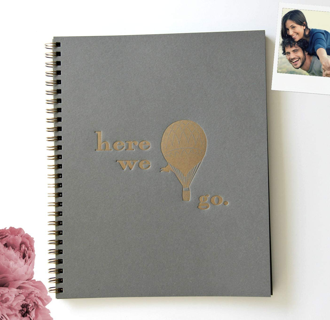 An image of a scrapbook in gray color with gold-embossed print on the cover.