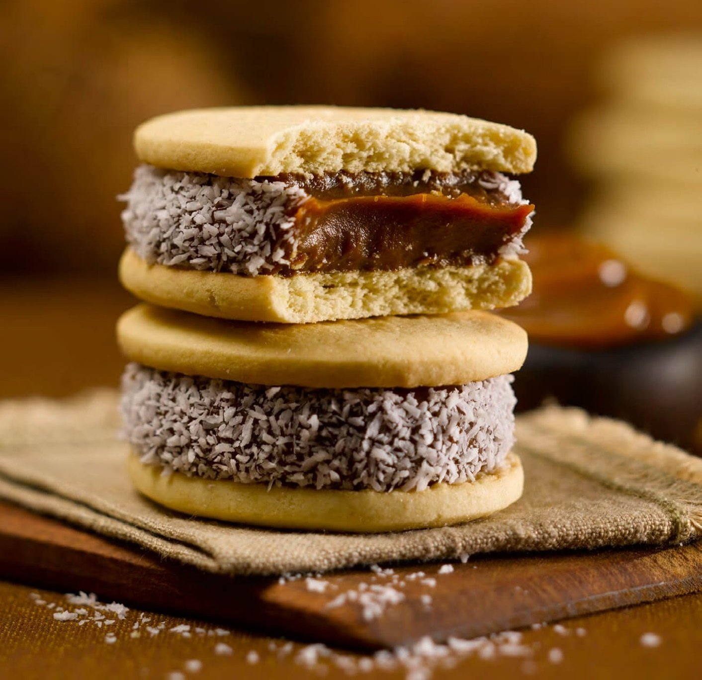 Cachafaz Alfajor Maizena - Cornstarch Sandwich Cookie filled with dulce de leche decorated with shredded coconut. 6 Units: 76 G