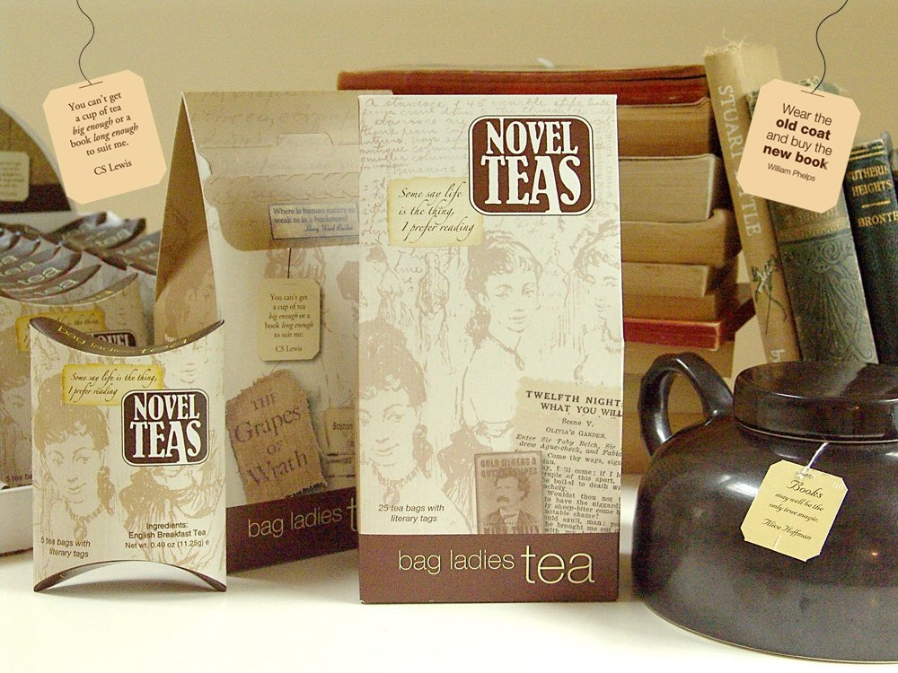 Several packages of Novel Teas teabags with a black kettle beside them.