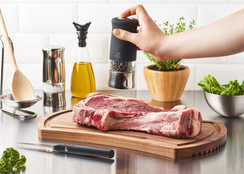 肉にペッパーミルで胡椒をかける