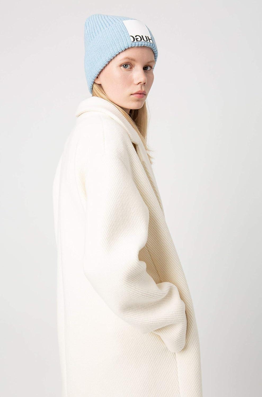 Frau mit blonden Haaren und weißer Mantel blaue Mütze Strickmütze Hugo Boss