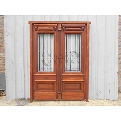 Puerta de entrada de madera antigua con rejas de hierro forjado