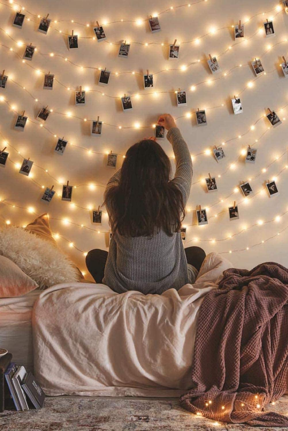 A girl attaching pictures to a photo clip LED string lights.
