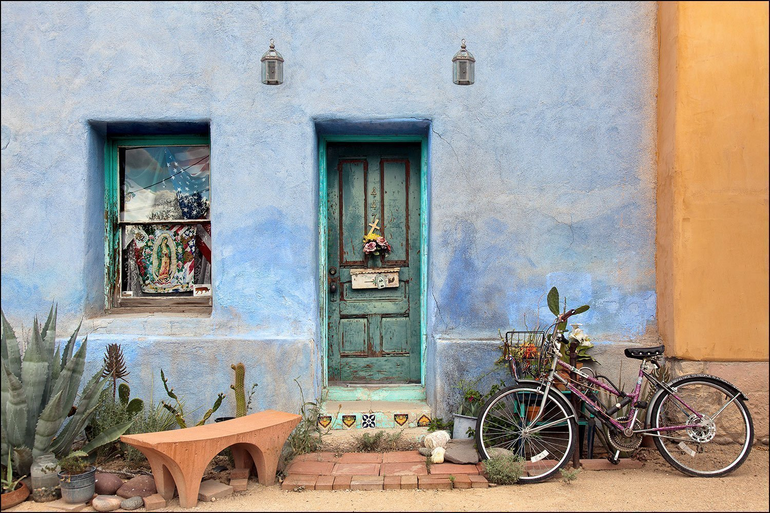 Photograph of colorful American Southwest urban scene with a green wood door, bike, cactus and blue adobe wall. Wall décor photography for over your couch or home artwork decorating needs.