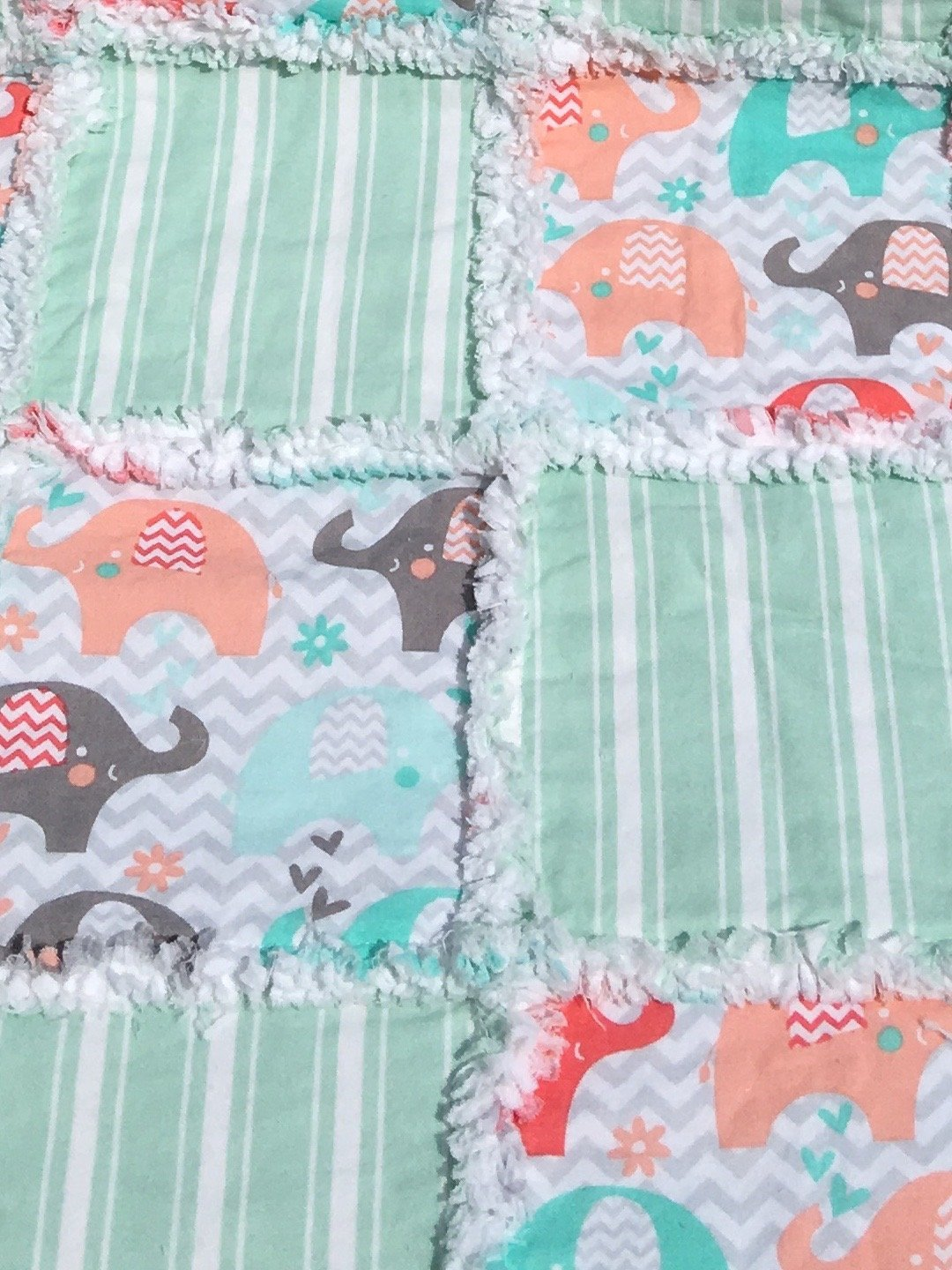 Baby quilt with colorful elephants in coral, peach, grey, and mint alternating with green stripes