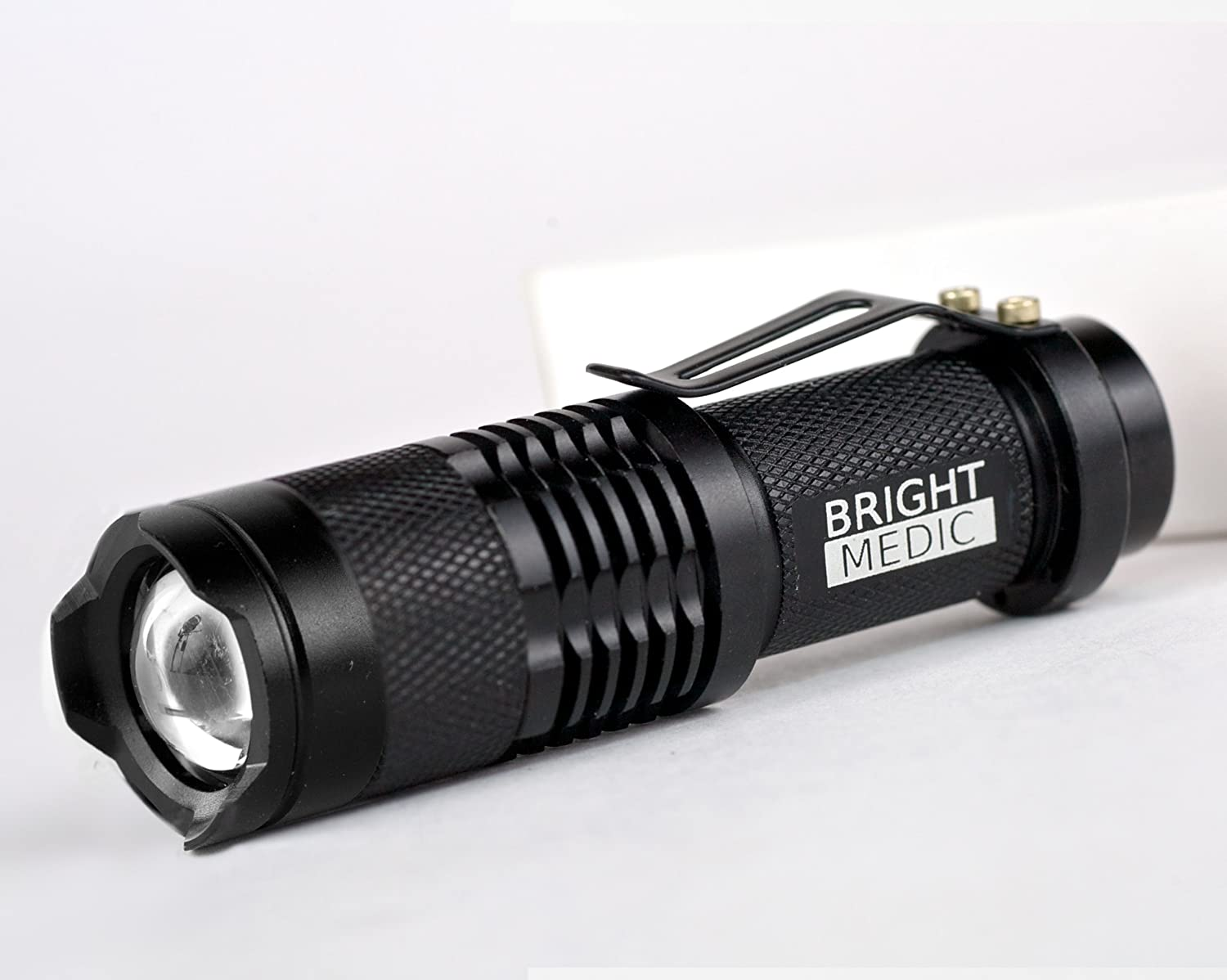 Image of the BrightMedic black flashlight on a white table.