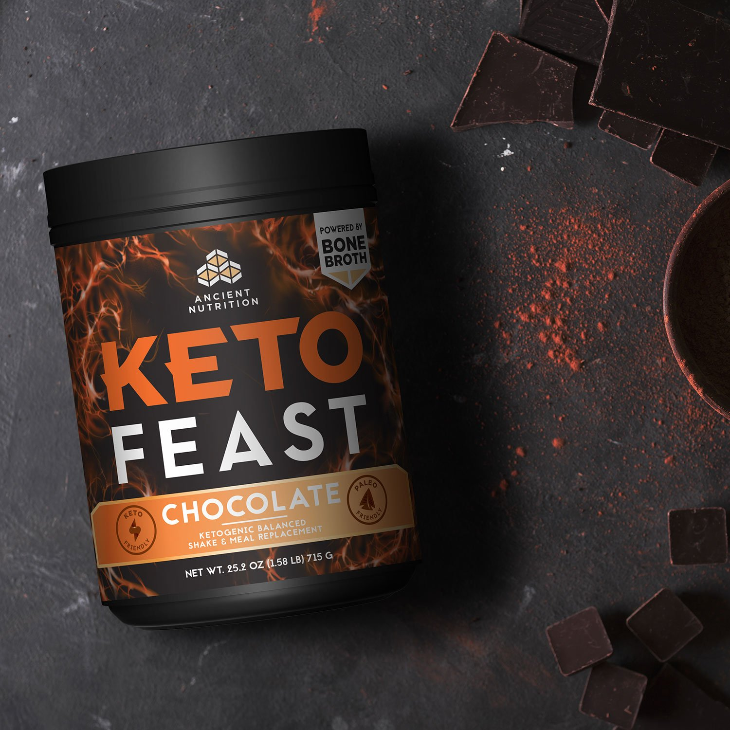 Keto feast bottle in a dark surface with dark chocolate around