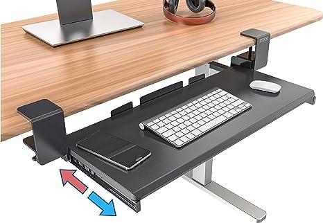 Abrazadera en la bandeja de teclado de la oficina bajo el ...