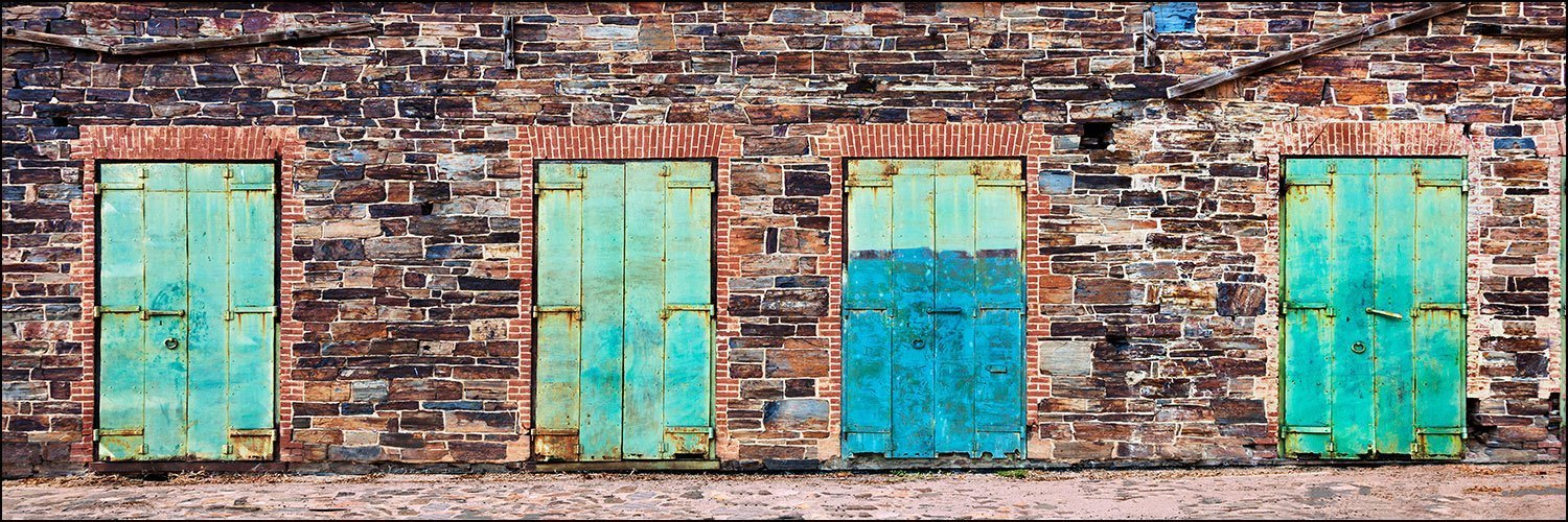 12 x 36 inch panoramic photograph of four industrial wood blue doors against a colorful brick and rock stone wall