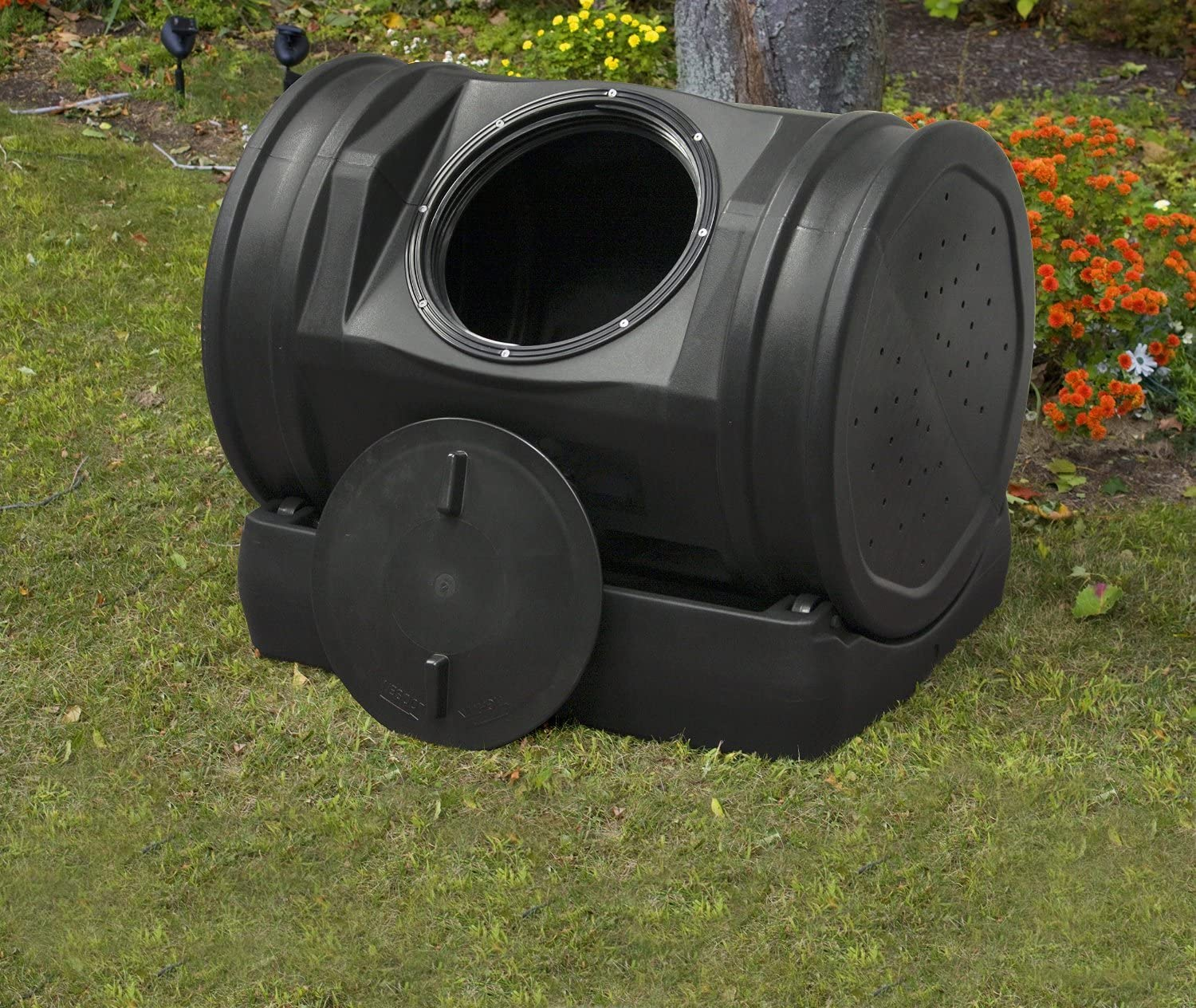 Hand turned compost tumbler on bed of grass.