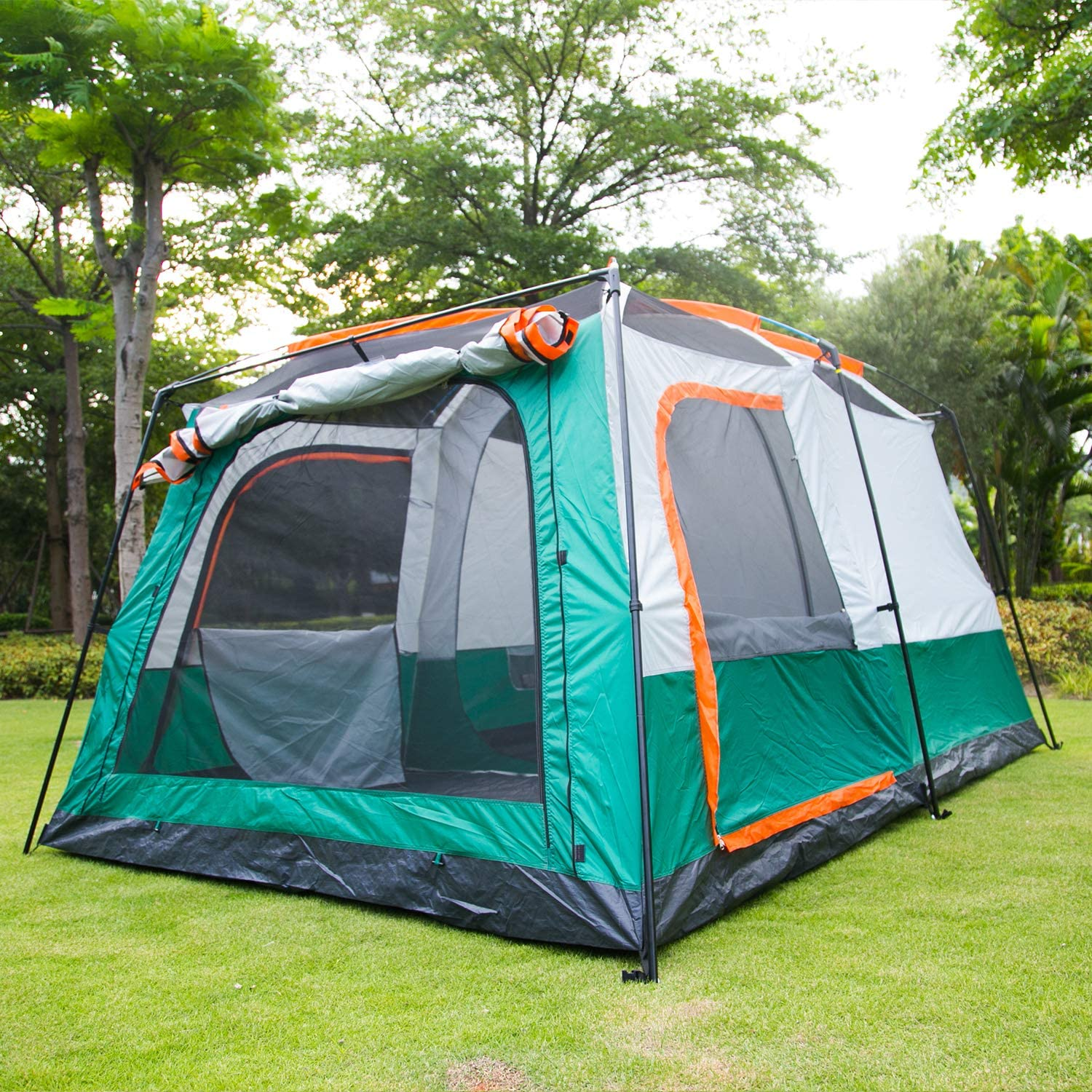 This is an image of a tent with wide screen doors and pitched on to a grassy lawn, trees at the back.