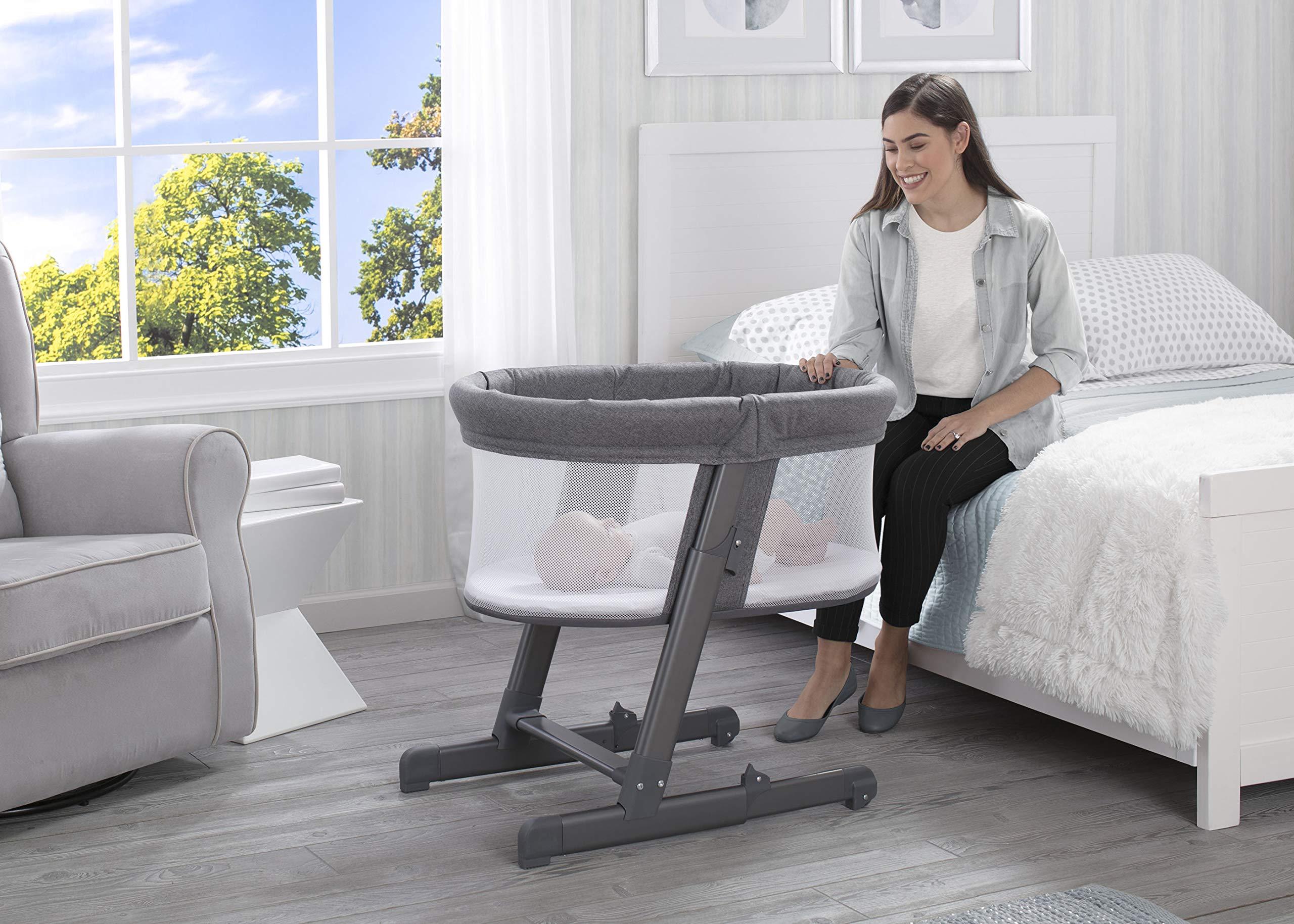 Simmons Kids Oval City Sleeper Bedside Bassinet – Adjustable Height Portable Crib with Wheels & Airflow Mesh, Grey Tweed