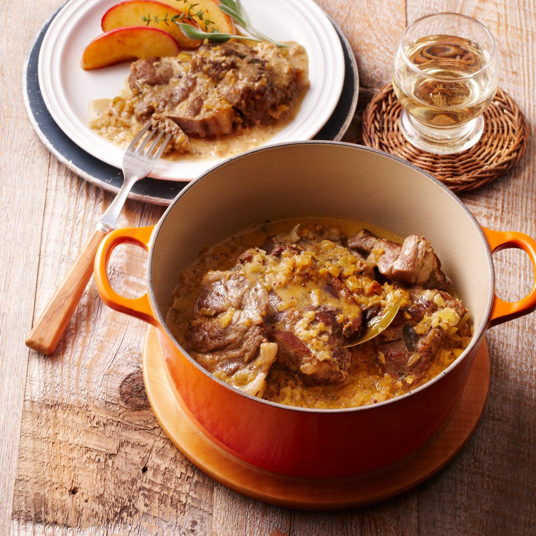 肉料理の入ったオレンジのお鍋と白いお皿