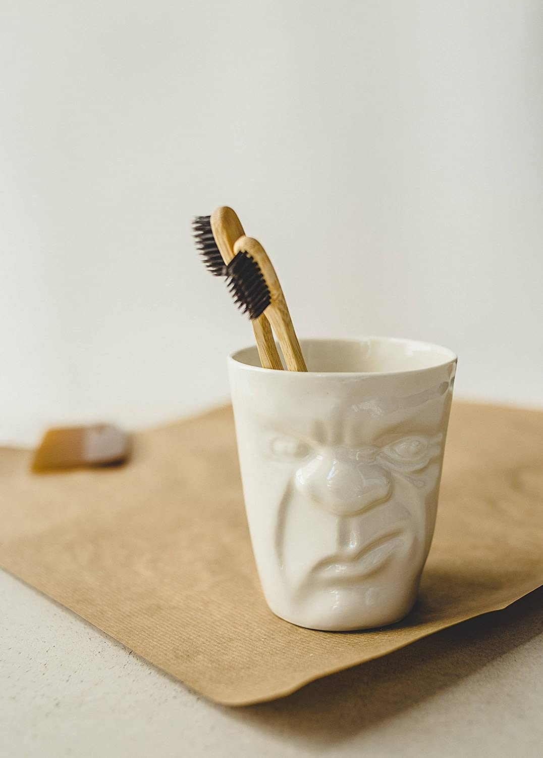 Modern white porcelain cup with a funny grumpy face for tea and cofee or toothbrushes pencils and makeup brushes storage by SIND studio