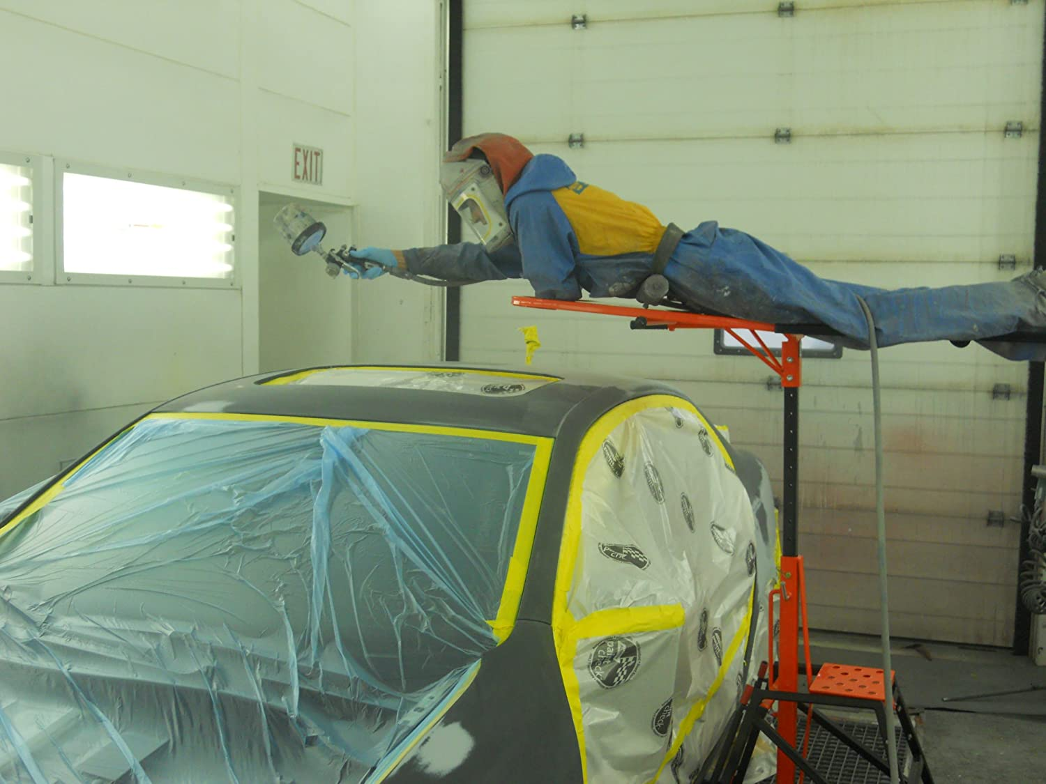 orange elevator model being used to paint roof of car